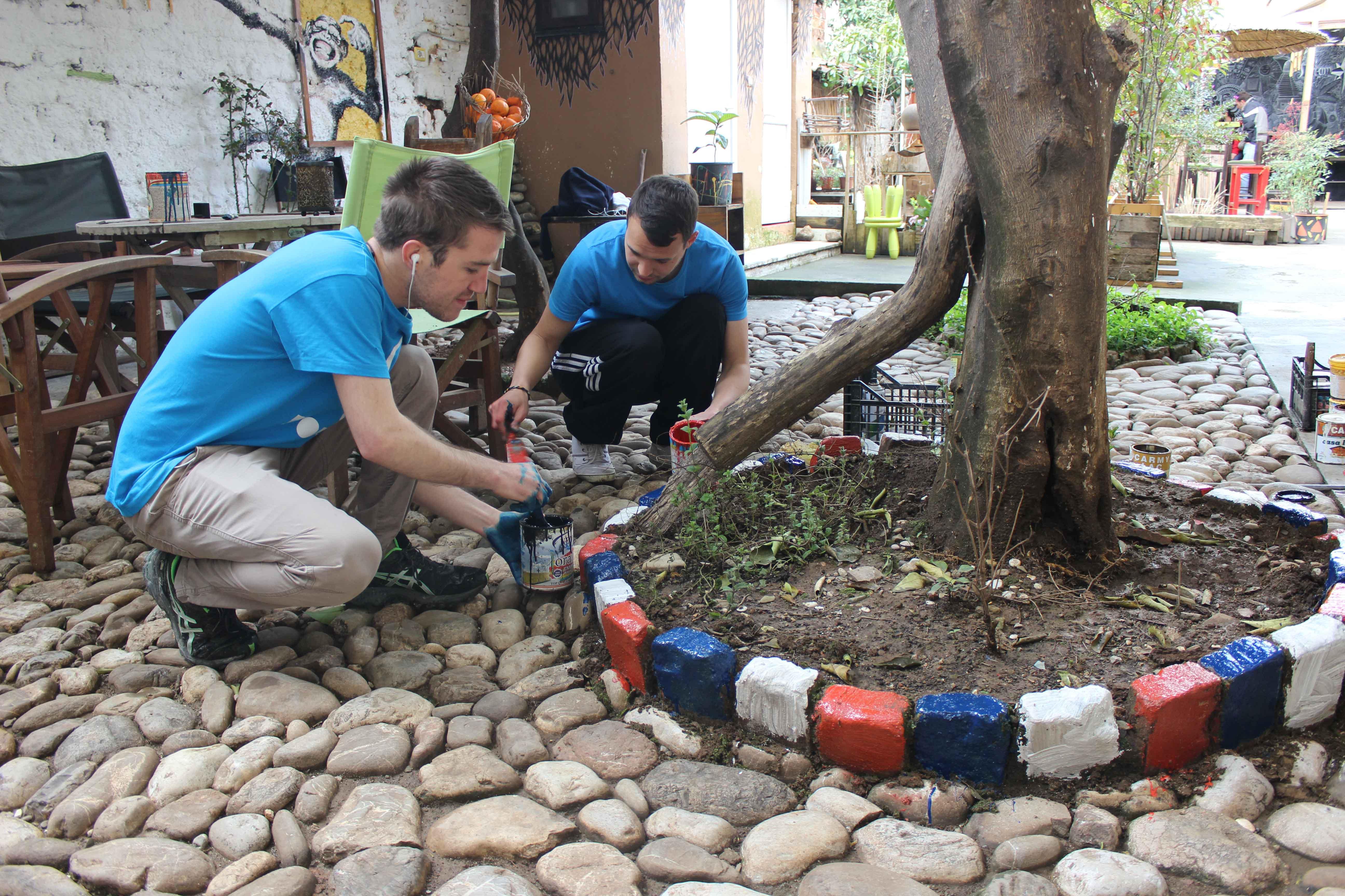Two hostel volunteers paining outside