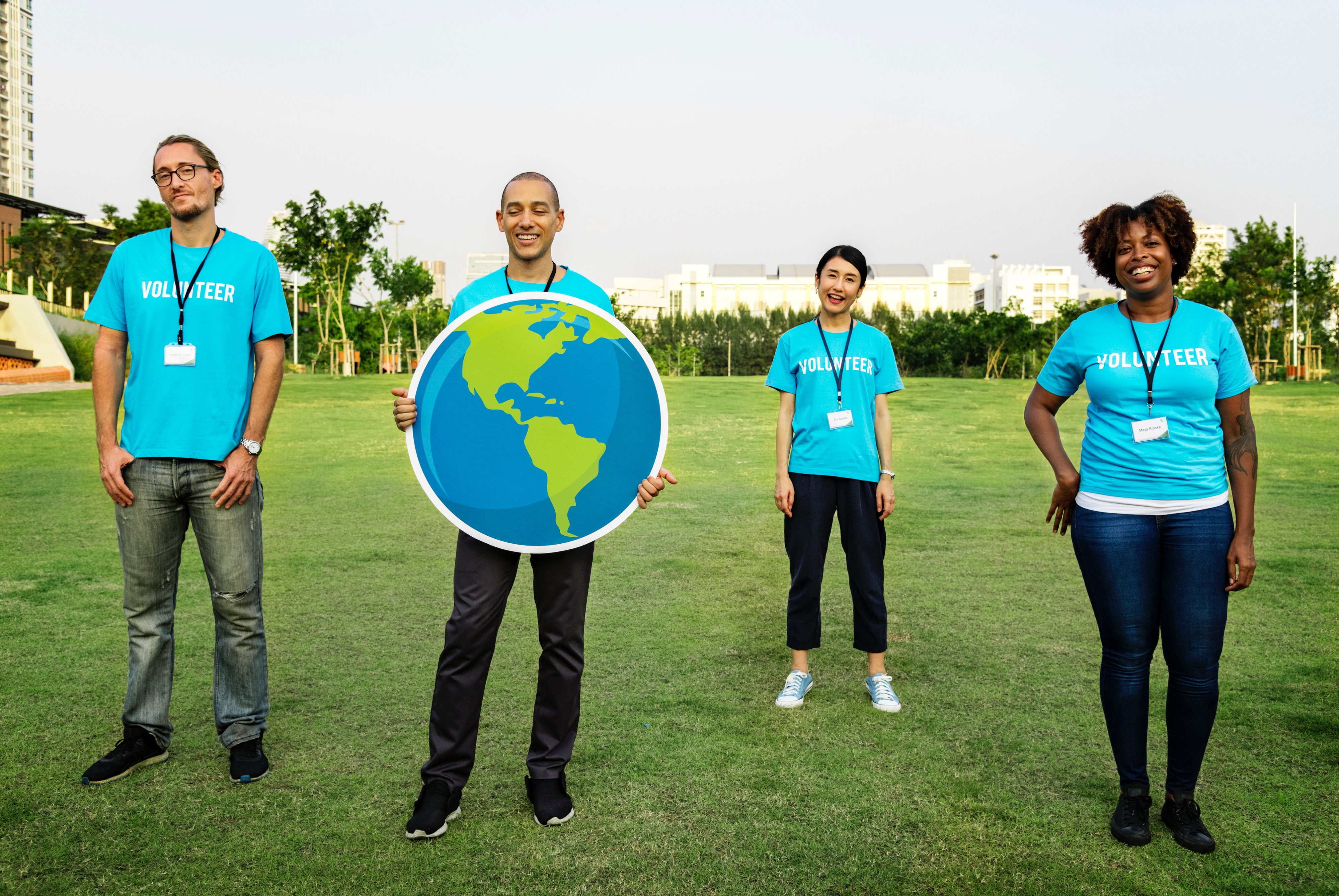 4 persons in blue Shirts outside with world sign