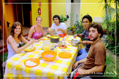 group-emjoy-food-table-condors-house-lima-peru-table-cloth-yellow-wall-plants-people-chair-fire-extinguisher-bowl-plats-jug