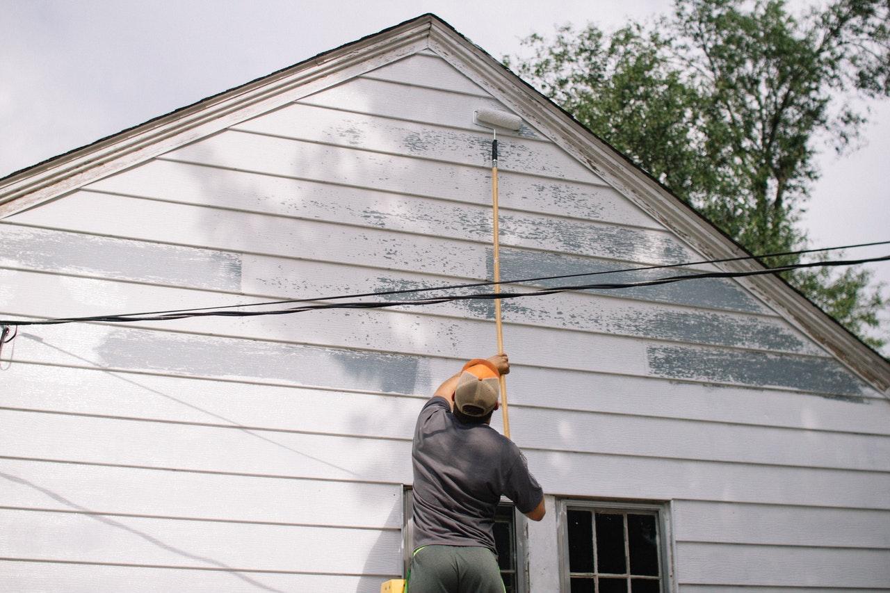 man painting exterior wall