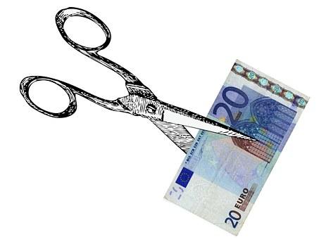 Metal scissors cutting a euro bill