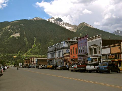 Downtown Silverton Colorado mountains green grass trees street cars traffic buildings town main people walking