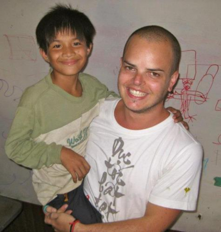 Vin with one of the Cambodian children while volunteering happy smile helping out