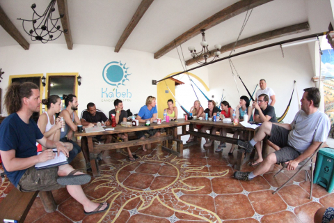 people sitting at a table in cancun discussing the hostel industry
