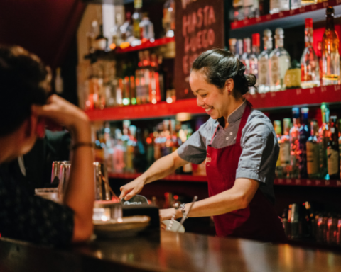 photo of bartender smiling while serving customers