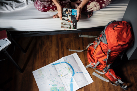person on bed with lonely planet book and backpack and map