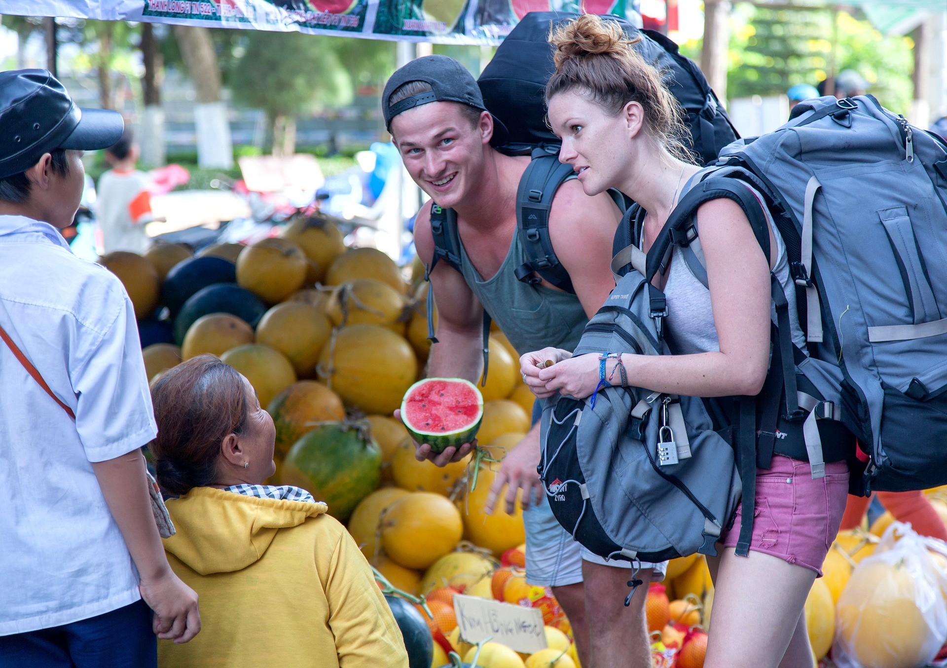 Backpacker man and woman in Vietnam at market with backpacks